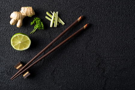 Chopsticks and food ingredients on black stone table top view