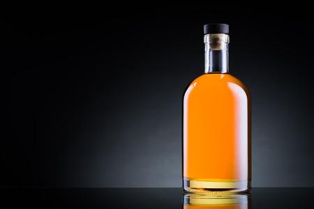 Photo pour Whiskey bottle on black glass surface - image libre de droit