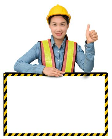female worker with Protection Equipment, posing behind big white banner, thumb up and looking at camera and copy space, isolated on white backgroundの写真素材