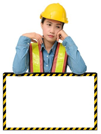 female worker with Protection Equipment, posing behind big white banner, scratching head, looking down and thinking and copy space, isolated on white backgroundの写真素材