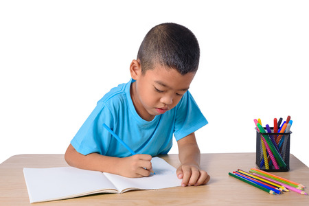 Foto de Cute cheerful child drawing using color pencil while sitting at table isolated on white background with clipping path - Imagen libre de derechos