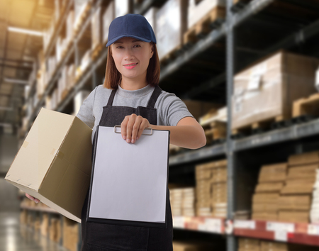 Photo for Female staff Delivering products Sign the signature on the product receipt form with parcel boxes Blurred the background of the warehouse - Royalty Free Image
