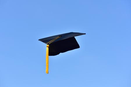 Photo pour Black hat of the graduates floating in the sky. - image libre de droit