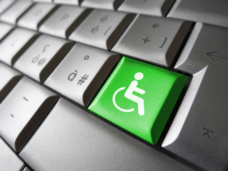 Web content accessibility concept with wheelchair icon and symbol on a green computer key for blog and online business.
