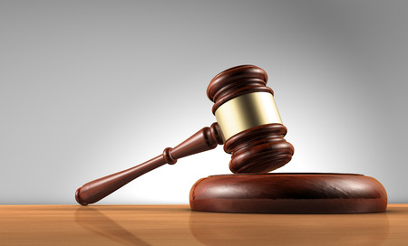 Judge, law, lawyer and Justice concept with a 3d render of a gavel on a wooden desktop with grey background.