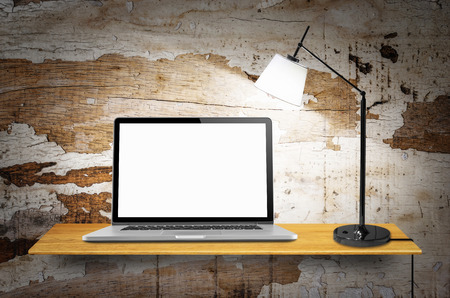 Laptop computer with blank screen and lamps on desk in the wall.