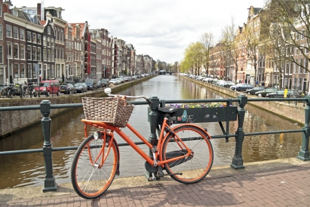 Orange bike on the bridge in Amsterdam city in the Netherlands