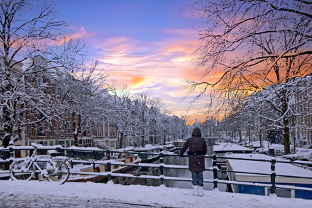 Foto de Amsterdam covered with snow  in winter in the Netherlands at sunset - Imagen libre de derechos