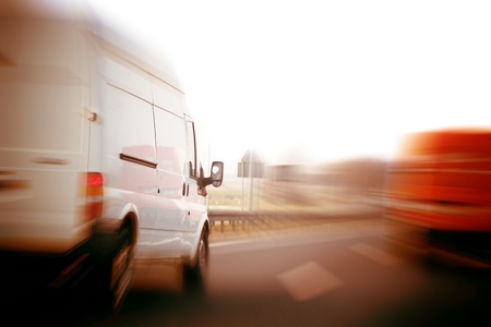 Transportation, logistics concept. Delivery vans, trucks on a freeway, speed motion blur.の写真素材