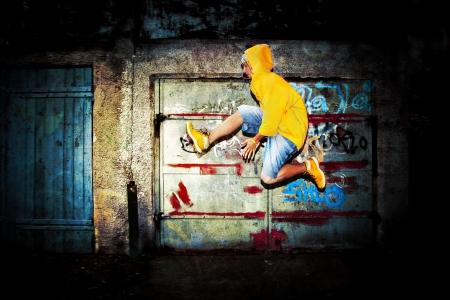 Young man jumping / dancing on grunge graffiti wall background
