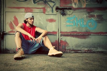 Young man sitting portrait on grunge graffiti wall