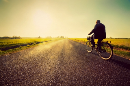 Old man riding a bike on asphalt road towards the sunny sunset sky
