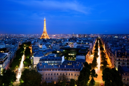 Skyline of Paris, France at night. View from Arc de Triomphe. The image with illuminated Eiffel tower being only a part of the city skyline is OK for commercial purposes