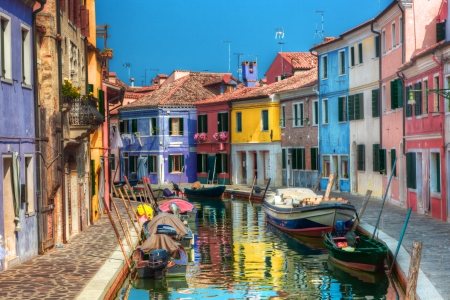 Colorful houses and canal on Burano island, near Venice, Italy. Sunny day.