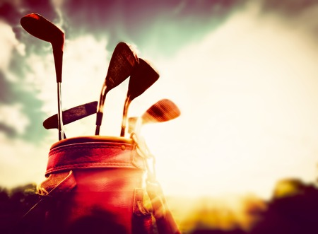 Photo pour Golf equipment in vintage, retro style. Professional clubs in a leather baggage at sunset - image libre de droit