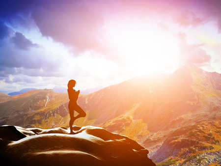 Woman standing in tree yoga position, meditating on rock in mountains at sunset  Zen, meditation, peace