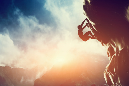 Photo pour A silhouette of man climbing on rock, mountain at sunset  Adrenaline, strenght, ambition - image libre de droit