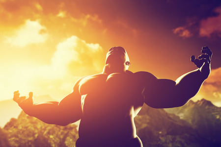 Foto de Very muscular strong man with hero, athletic body shape expressing his power and strength on the peak of the mountain at sunset - Imagen libre de derechos