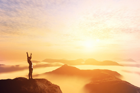 Happy man with hands up on the top of the world, above clouds and mountains. Success, winner, bright future