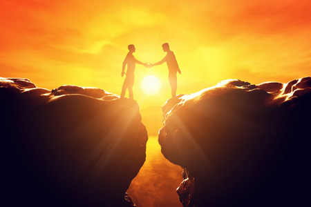 Photo pour Two men shake hands over precipice between two rocky mountains at sunset. Business, deal, handshake, connection concepts - image libre de droit