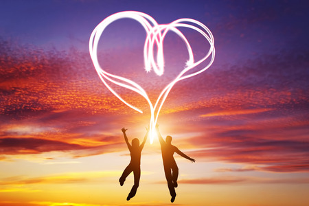 Photo for Happy couple jump together and make a heart symbol of light manifesting their love. Romantic sunset sky, Valentines Day. - Royalty Free Image