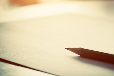 Pencil lying on blank piece of paper in morning light. Creative work, writing, drawing etc. Vintage natural mood