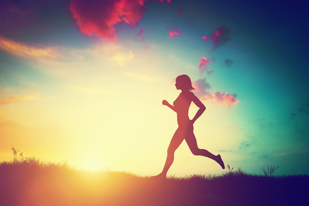 Silhouette of a fit woman running at sunset. Training, jogging, healthy lifestyle.