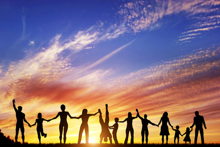 Photo pour Happy group of diverse people, friends, family, team standing together holding hands and celebrating success. Sunset sky - image libre de droit