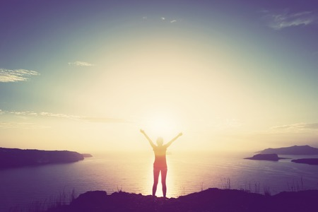 Photo pour Happy woman with hands up standing on cliff over sea and islands at sunset.  - image libre de droit