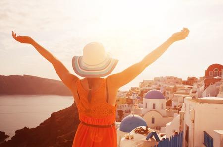 Happy woman in sun hat enjoying her holidays on Santorini, Greece.