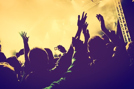 Concert, disco party. People with hands up having fun in night club lights. Vintage mood