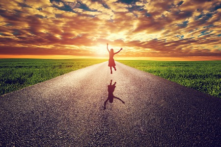 Foto de Happy woman jumping on long straight road, way towards sunset sun. Travel, happiness, win, healthy lifestyle concepts. - Imagen libre de derechos