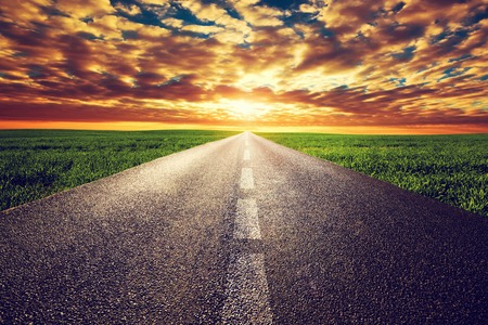 Foto de Long straight road, way towards sun. Sunset sky, travel, transport, destination concepts. - Imagen libre de derechos