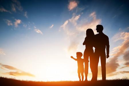 Foto de Happy family together, parents with their little child at sunset. Boy reaching the sun - Imagen libre de derechos