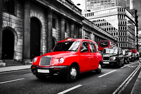 Symbol of London, the UK. Taxi cab known as hackney carriage.. Black and white with red. Iconic English transportation, red buses in the background
