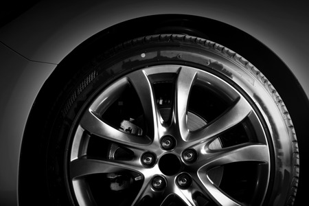 Close-up of aluminium rim of luxury car wheel. Detail background