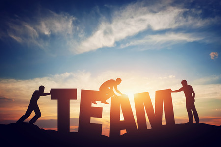 Foto de People connect letters to compose the team word. Teamwork concept, idea. Sunset positive light. - Imagen libre de derechos