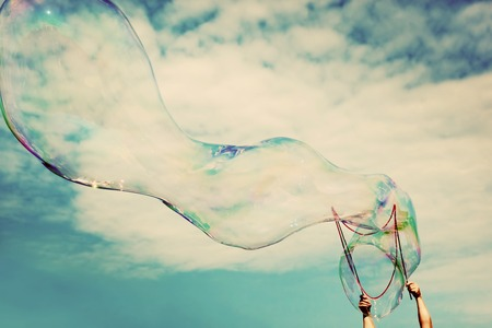 Photo for Blowing big soap bubbles in the air. Vintage freedom, summer concepts. Puffy clouds sky. - Royalty Free Image