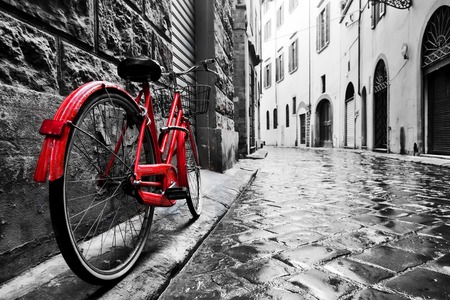 Foto de Retro vintage red bike on cobblestone street in the old town. Color in black and white. Old charming bicycle concept. - Imagen libre de derechos