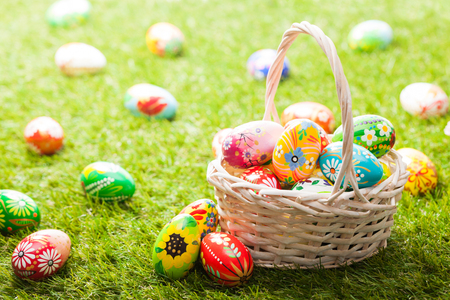 Foto per Unique hand painted Easter eggs in basket on grass. Traditional decoration in sun light - Immagine Royalty Free