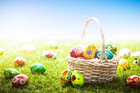 Photo for Unique hand painted Easter eggs in basket and lying on grass, blue sky. Traditional decoration in sun light - Royalty Free Image