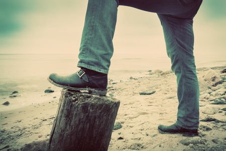 Man in jeans and elegant shoes leaning against tree trunk on wild beach looking at sea. Vintage, concepts of musculinity, confidence, mystery etc.