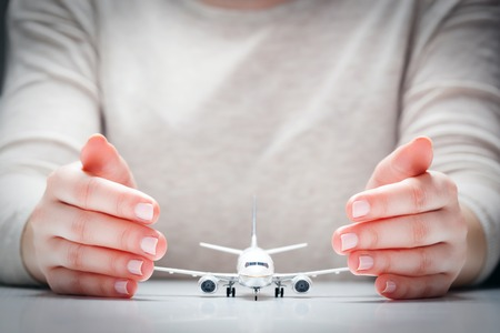 Photo pour Airplane model surrounded by hands in gesture of protection. Concept of aircraft industry, airline safety, security and insurance. - image libre de droit