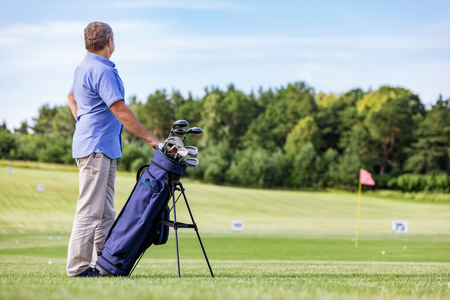 Senior man standing proudly on a golf club, holding a golf bag with clubs. Confidence and enjoyment.