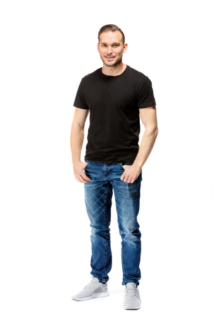 Photo pour Casual, relaxed man in a black t-shirt, looking straight into the camera. Isolated on white background. Full body shot. - image libre de droit