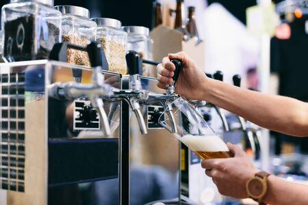 Foto de Bartender pouring craft beer from a tap at beerfest. Focus on glass and tap - Imagen libre de derechos