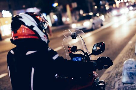 Photo pour Woman on motorbike in the city at night. About to enter the traffic - image libre de droit
