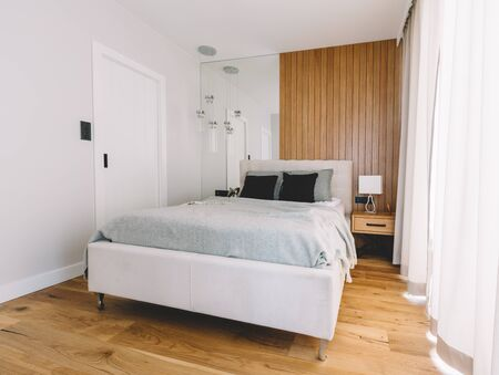 Photo pour Small cozy bedroom with comfortable bed and wooden floor. Clean modern interior design - image libre de droit