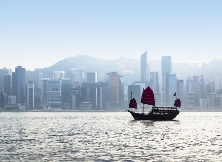 Junk Boat in Hong Kong harbor with cityscape under fog in background