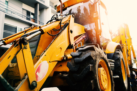 Close up of yellow construction vehicle parking in the construction site of town home building